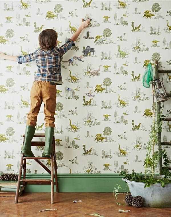A little kid playing with the magnetic wallpaper