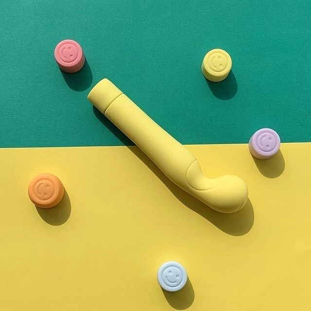 the tennis coach vibrator against a yellow and green background with smiley face buttons throughout