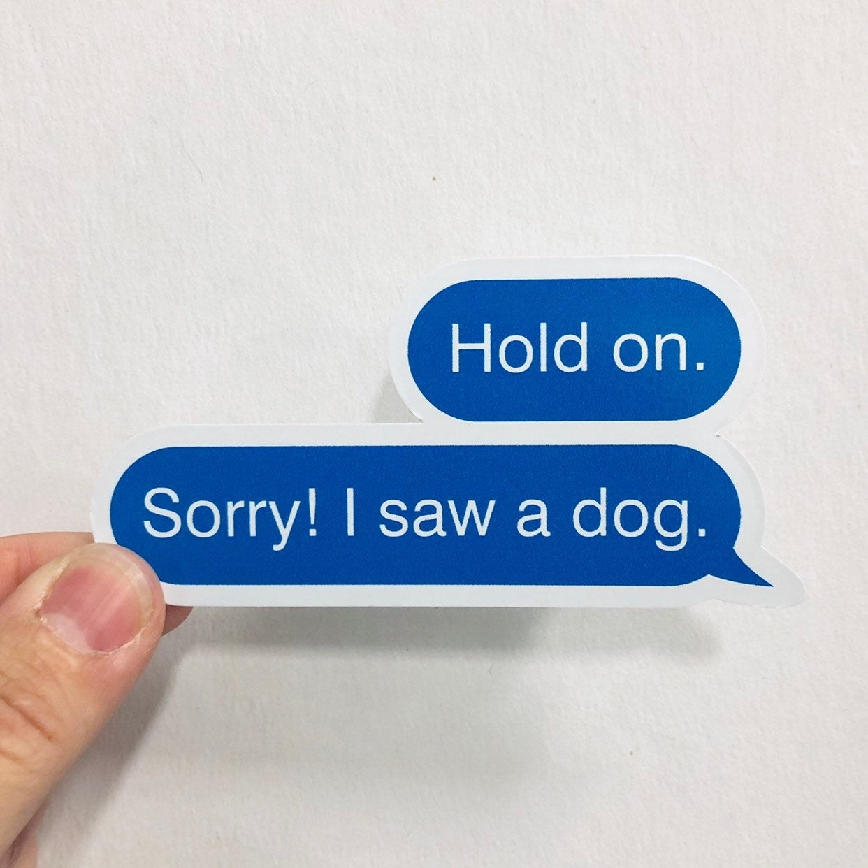 "A text message vinyl sticker that reads, ""Hold on. Sorry! I see a dog."""