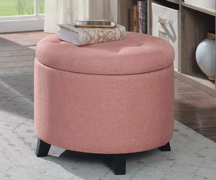A round light pink tufted ottoman with a removable top lid