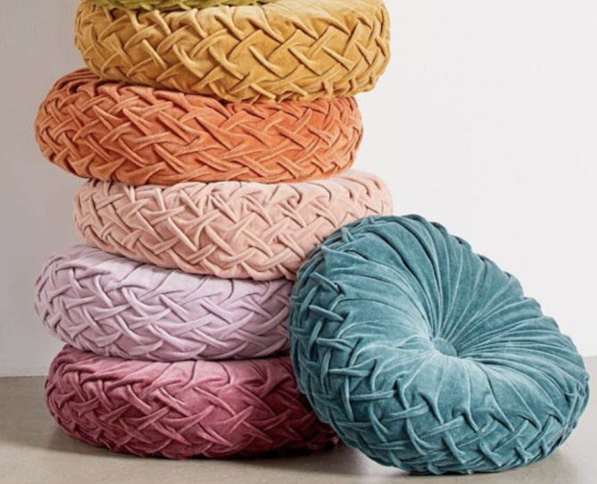 Round pintuck pillows stacked on top of each other in jewel tones