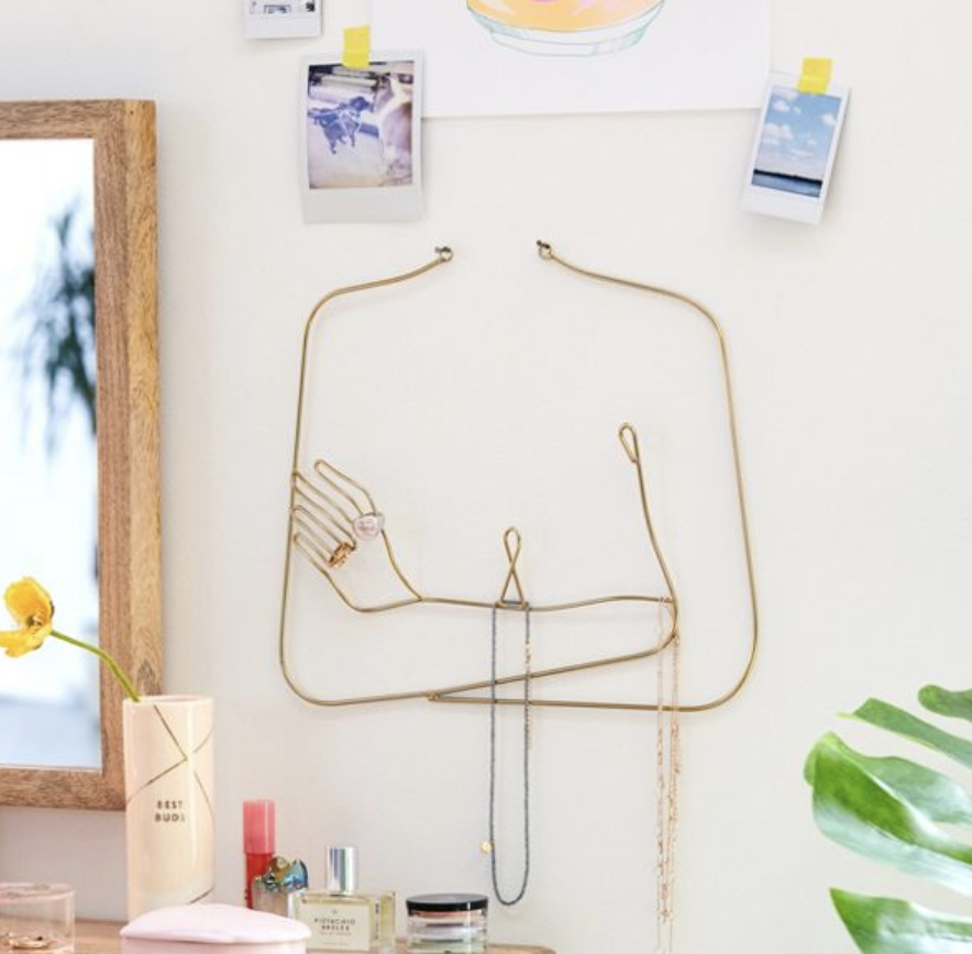 A minimalist gold wall hanging of a bust in the shape of someone crossing their arms over their chest