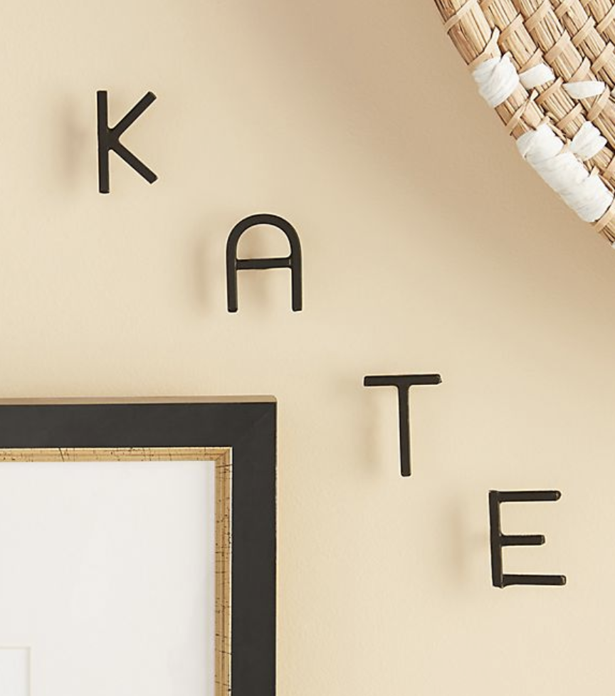 "Black minimalist letters hooked into a wall to spell ""KATE"""