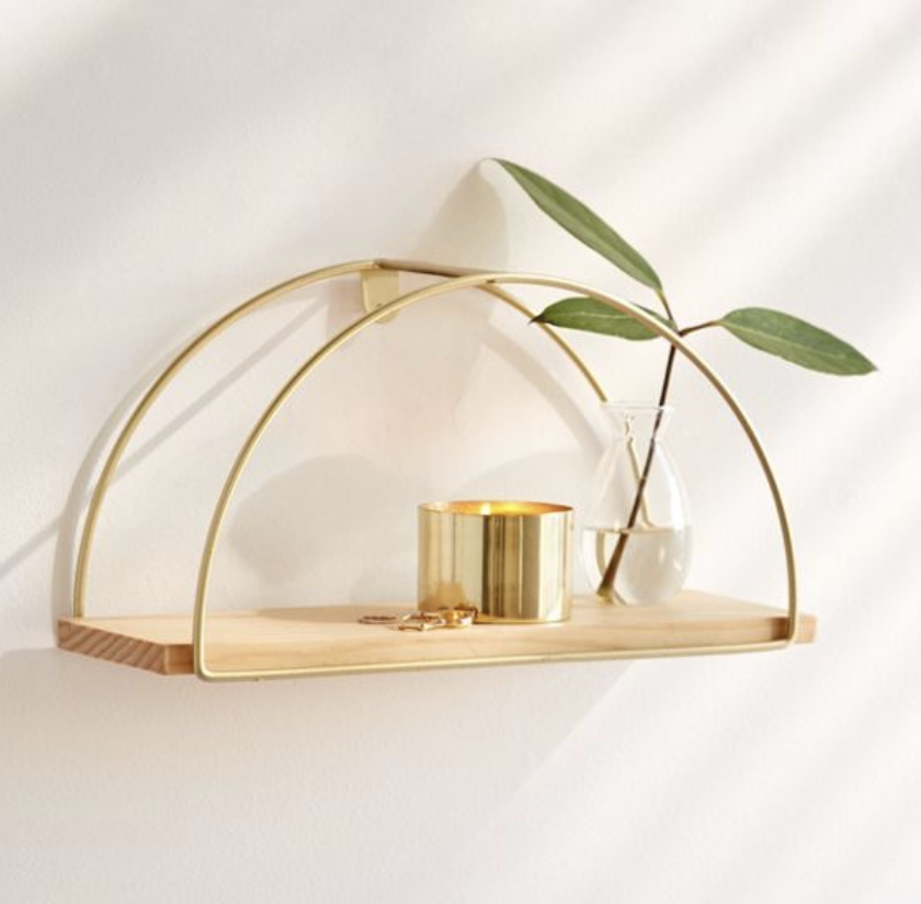 A wooden based shelf framed with gold demi-circle wires mounted to a wall