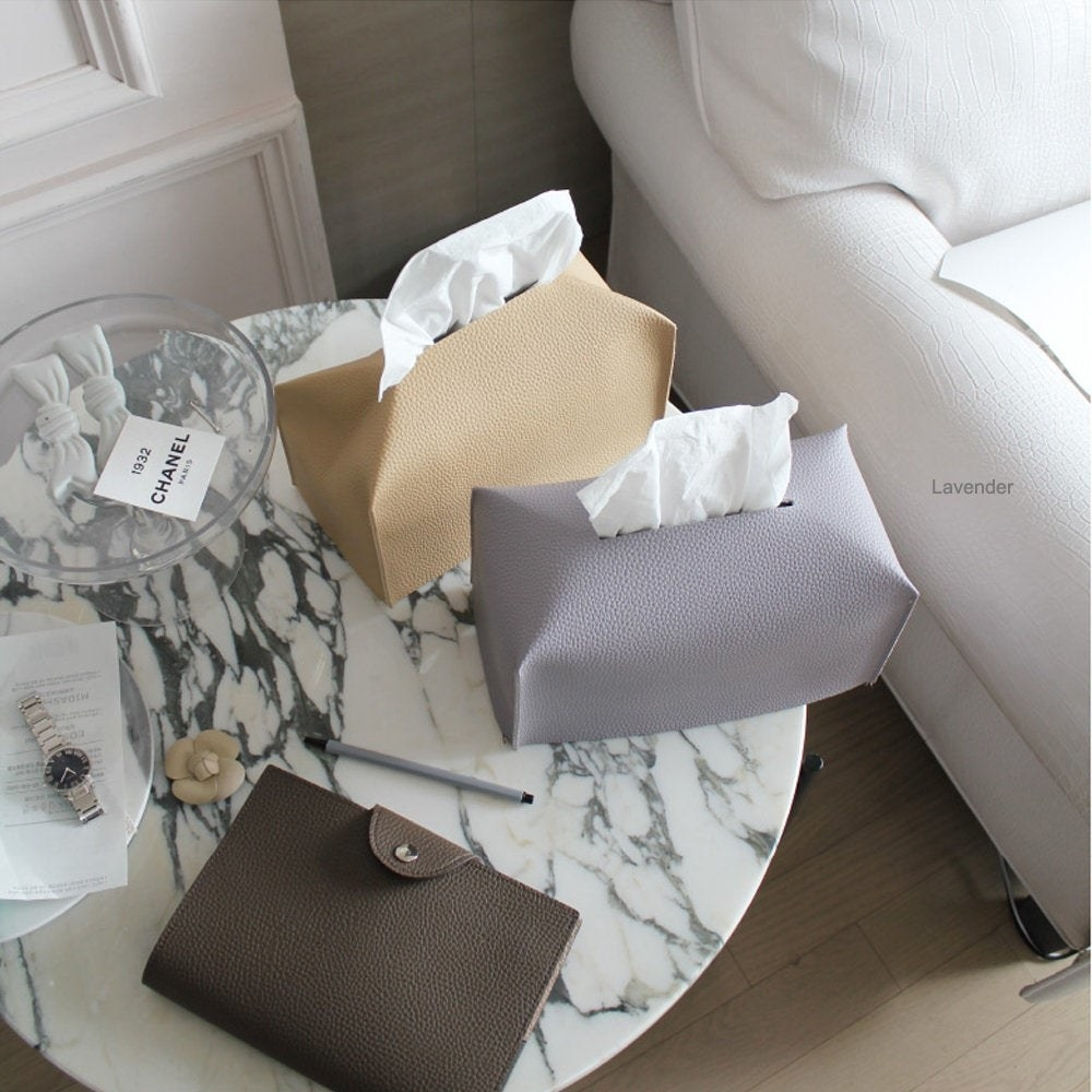 lavender and tan faux leather tissue box covers over a box of tissues