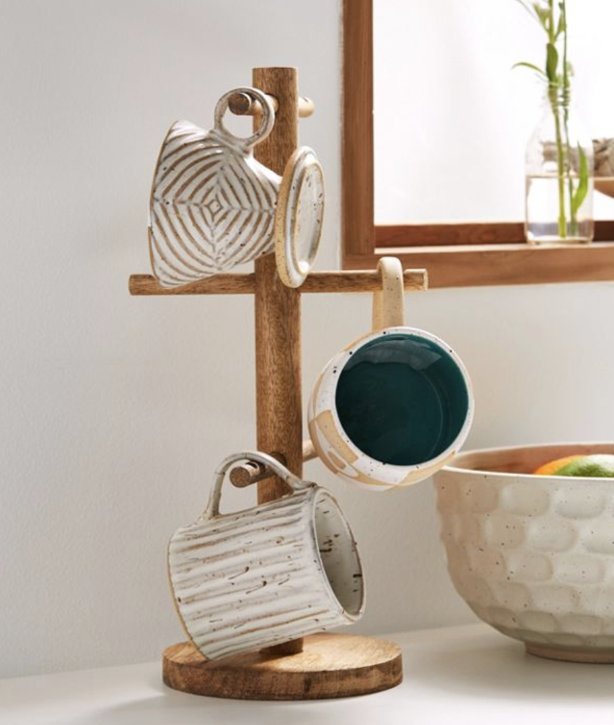 """A wood mug tree with a round base and six """"branches"""" to hold mugs"""