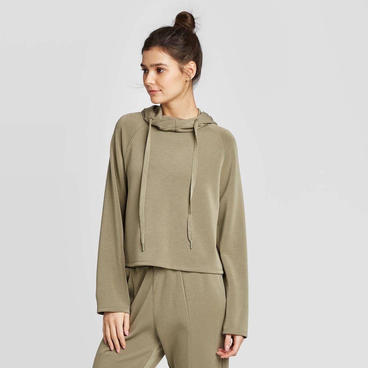 model wearing the hoodie in moss green