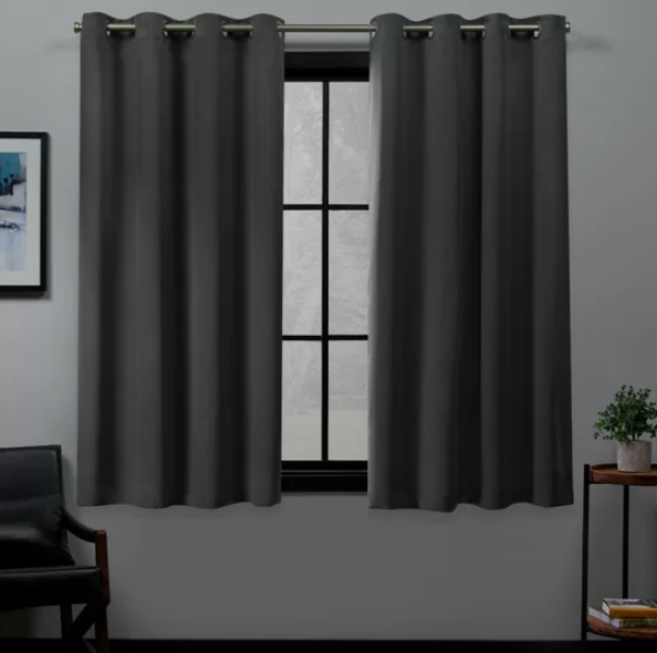 A pair of gray curtains semi-covering a window