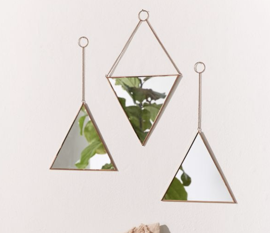 Three small triangular mirrors hung with dangling metal chains to the wall