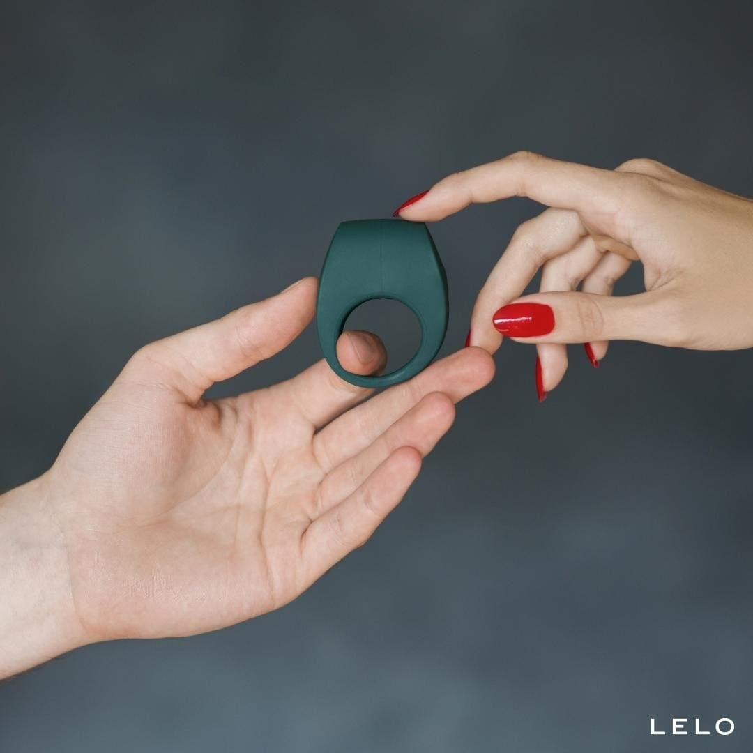 Two hands holding the forest green–colored sex toy
