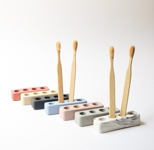 The holders in a variety of colors showing how toothbrushes fit in them