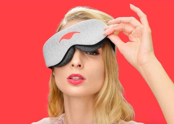 A model wearing the sleep mask and lifting one eye