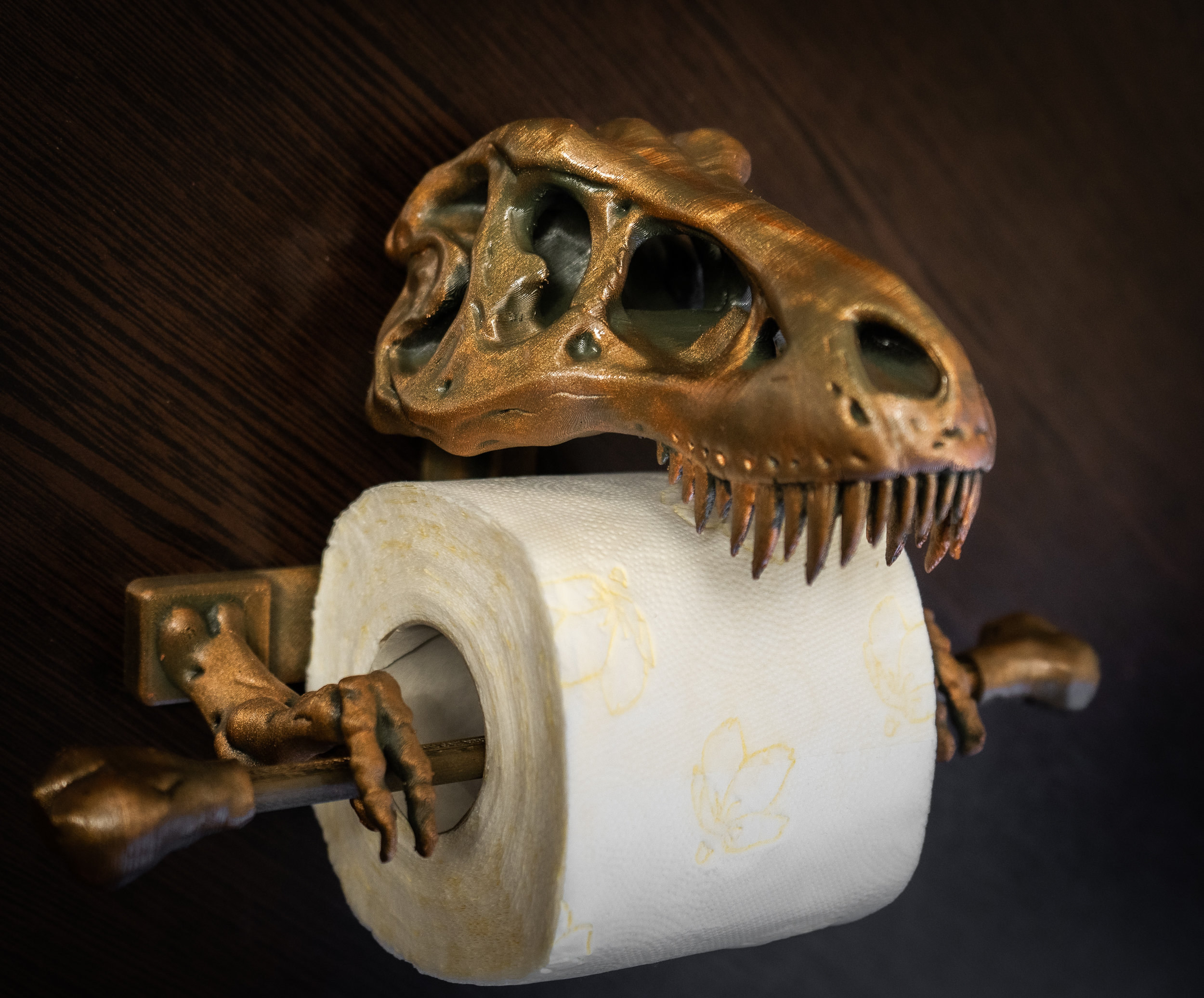 a bronze t-rex skull with little arms holding a roll of toilet paper