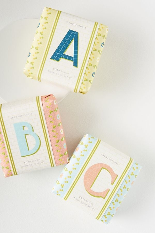 three bars of soap wrapped in colorful paper and each sporting an initial