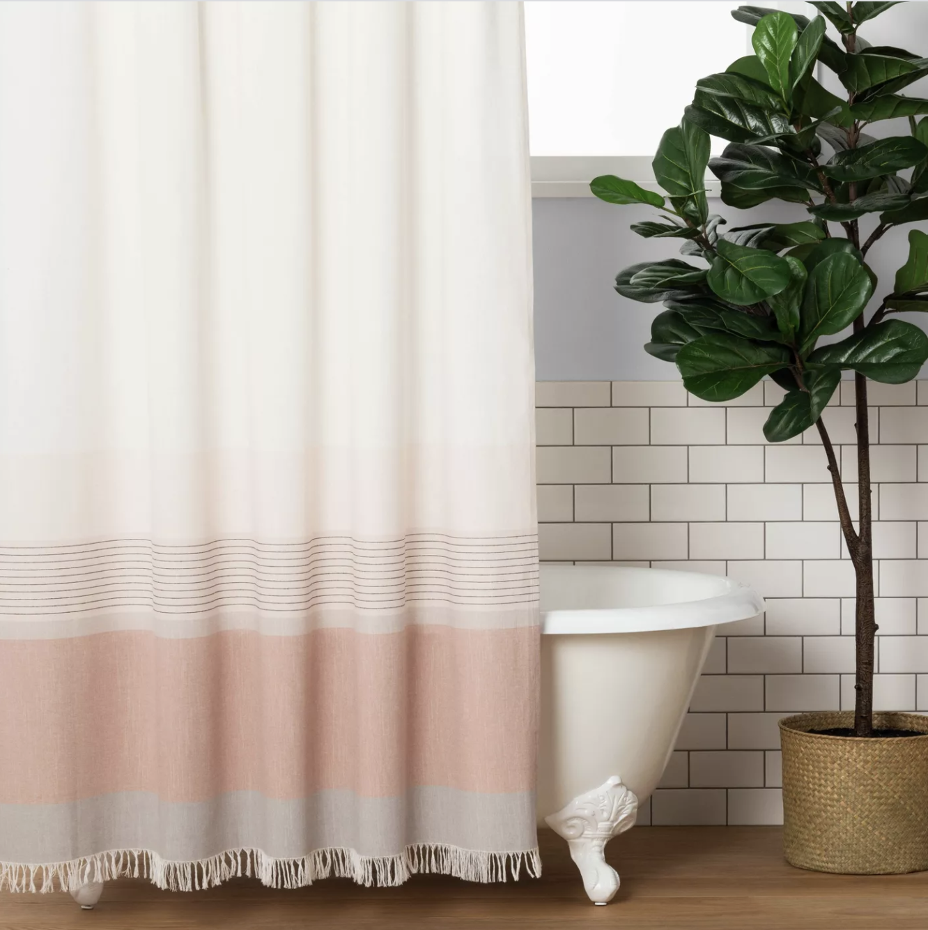 a white shower curtain with a pink ombre design towards the bottom and fringe on the end