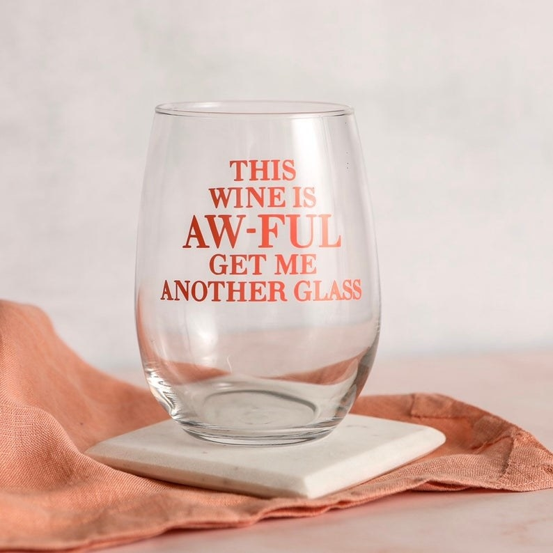 "The stemless glass that reads ""This wine is aw-ful get me another glass"""
