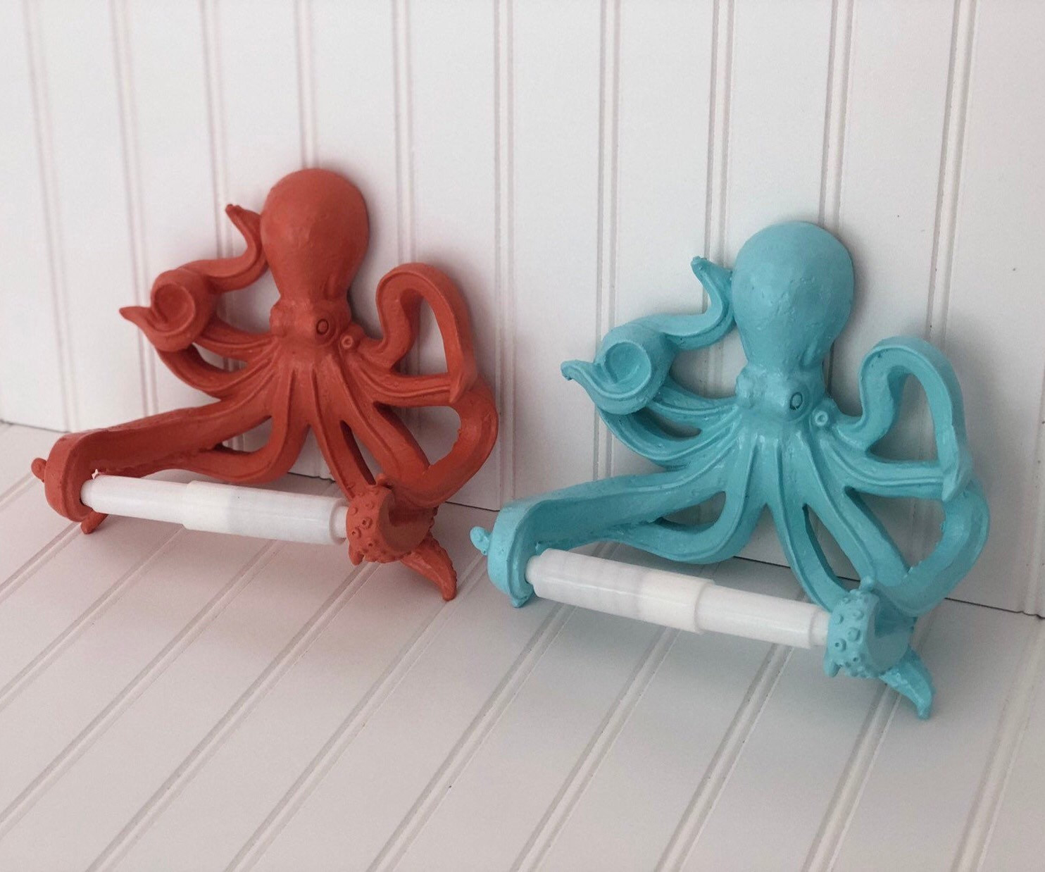 a blue and a red octopus shaped toilet paper roll holder