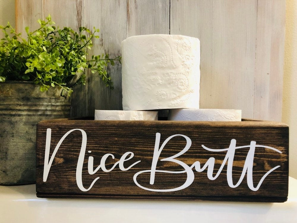 """a wooden open box that says """"nice butt"""" in white script"""