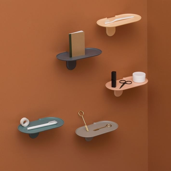 an array of tiny oval shelves attached to the wall with small bathroom items on them