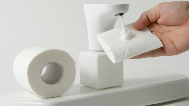 a model holding a piece of toilet paper under the fohm dispenser as it expels foam