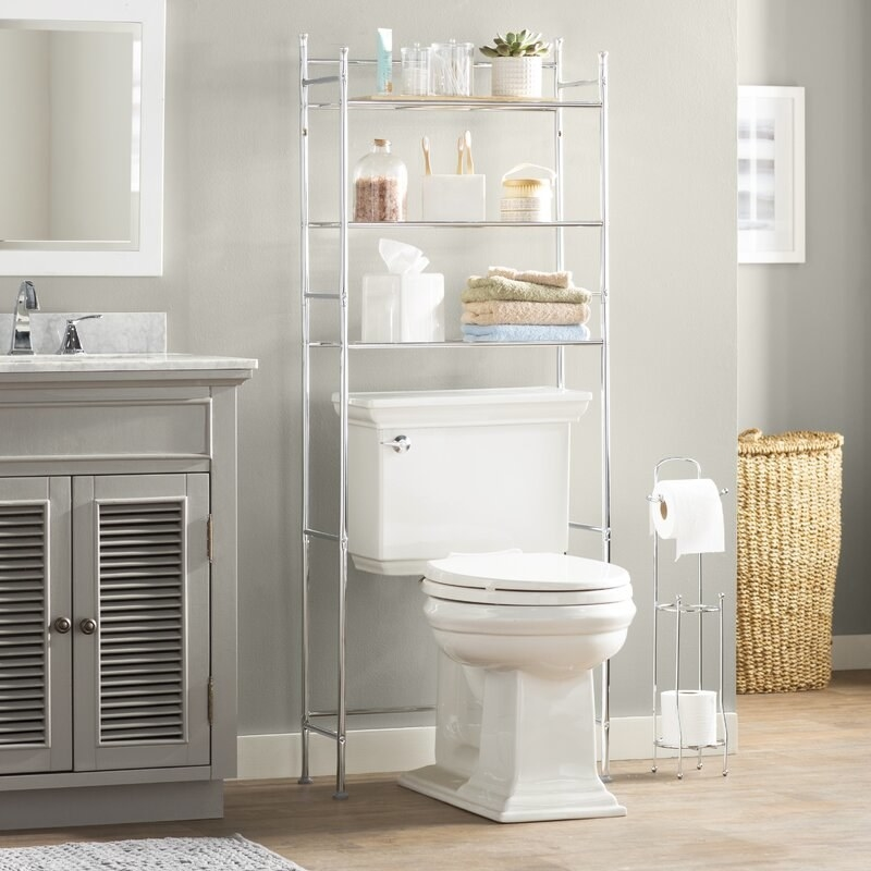a thin metal shelving unit with three shelves that fit over and around a toilet