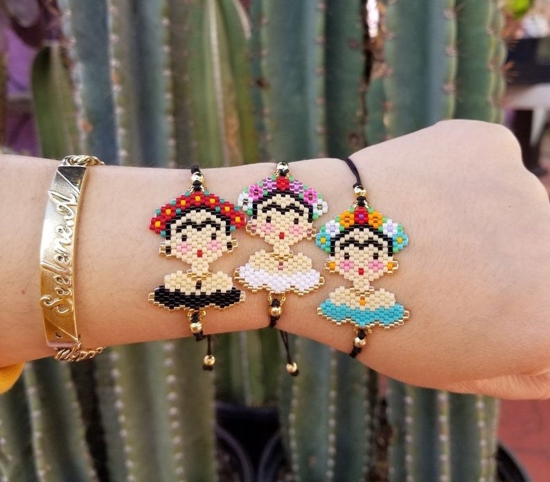 A person wearing three different Frida bracelets in different varieties.