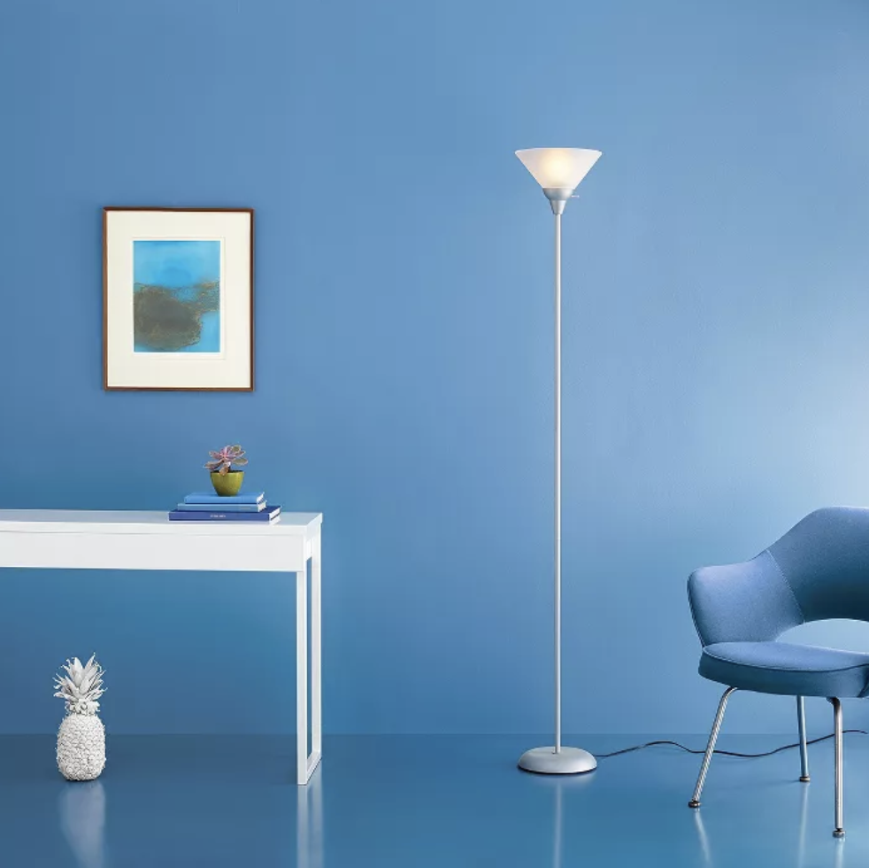 A gray tall floor lamp with a round base and an upside down triangular top light fixture