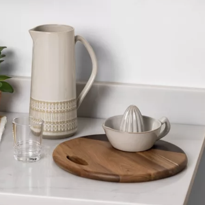 A wooden circular serving board with a dark brown accent on the side and a handle on a counter