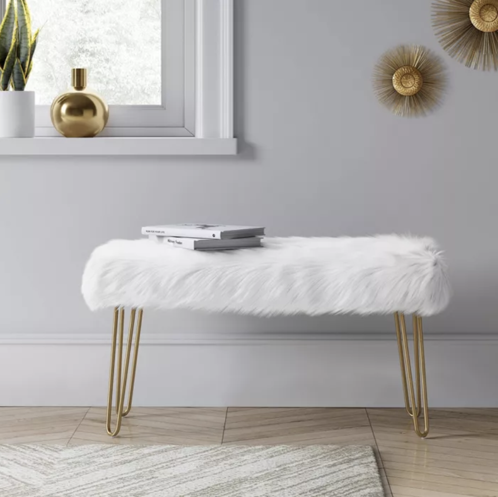 A hairpin bench with gold legs and a white faux fur top