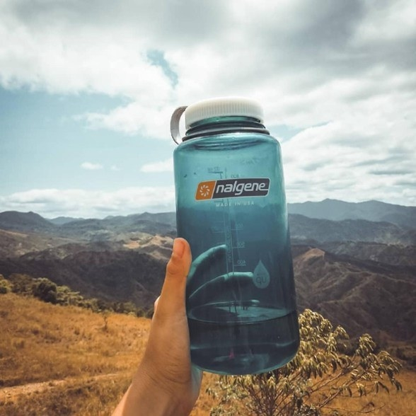 A person holding up their water bottle while hiking in the mountains