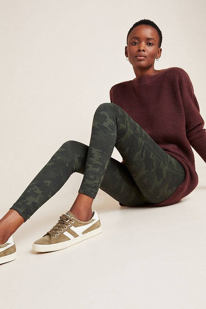 Model sitting on the floor while wearing the Spanx seamless leggings in camo.