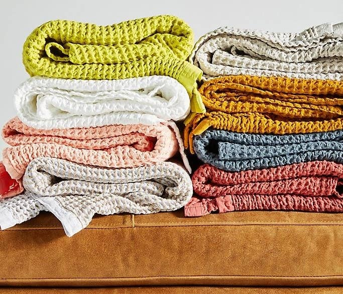 Folded piles of the waffle throw blankets in multiple colors.