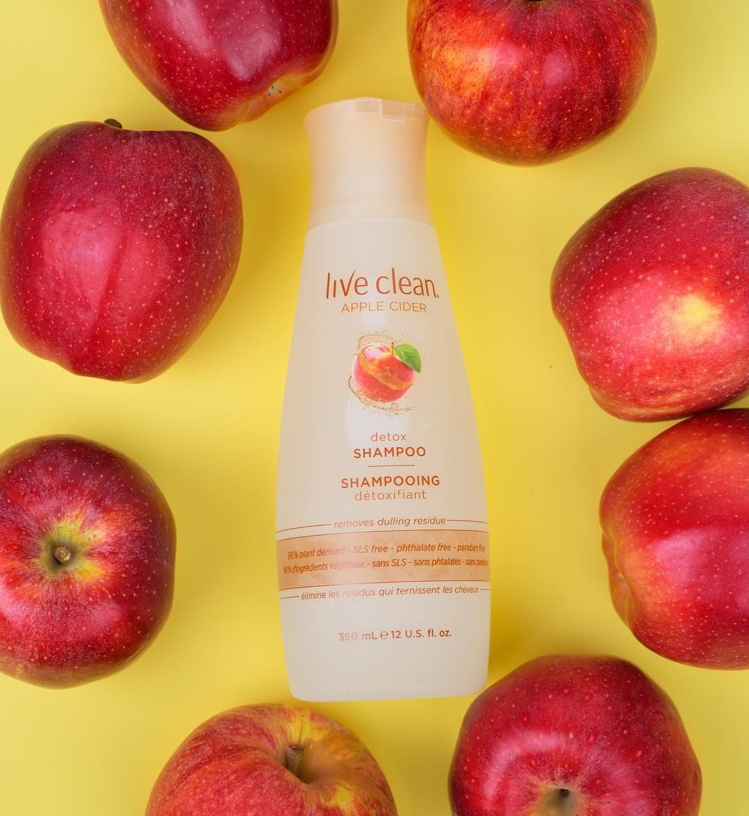 A bottle of shampoo with a circle of apples placed around it