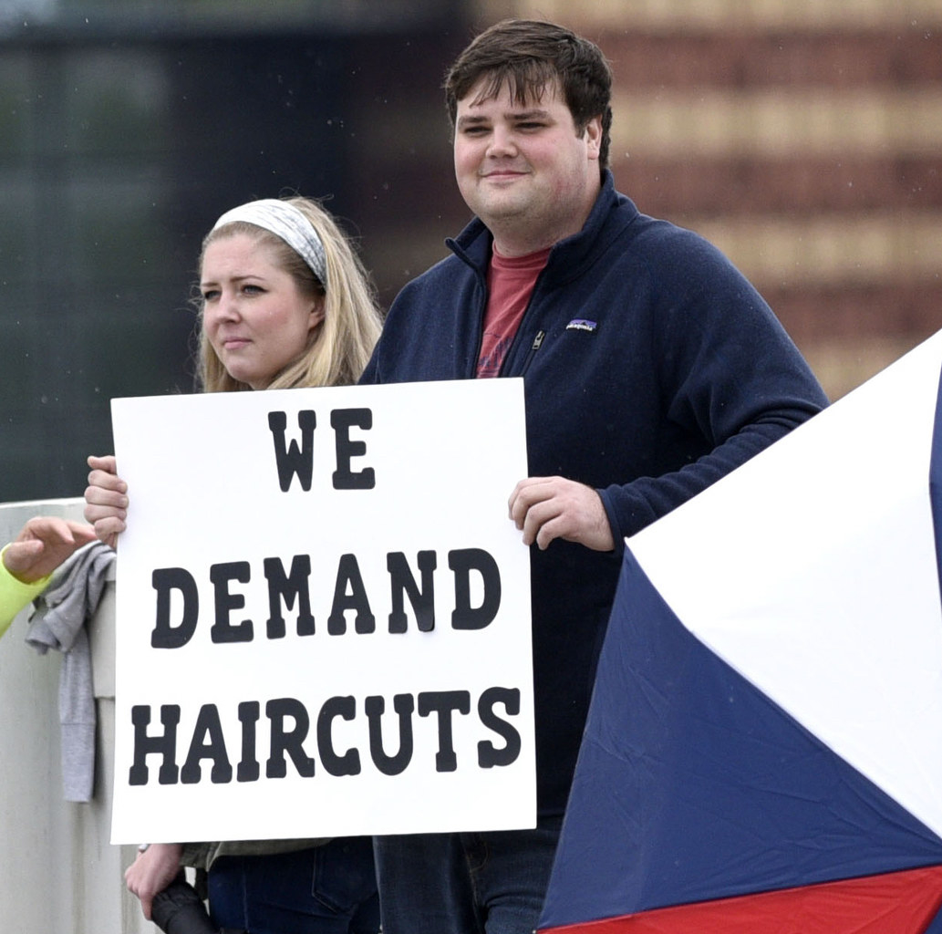 """Man and woman with a sign reading, """"We demand haircuts"""""""