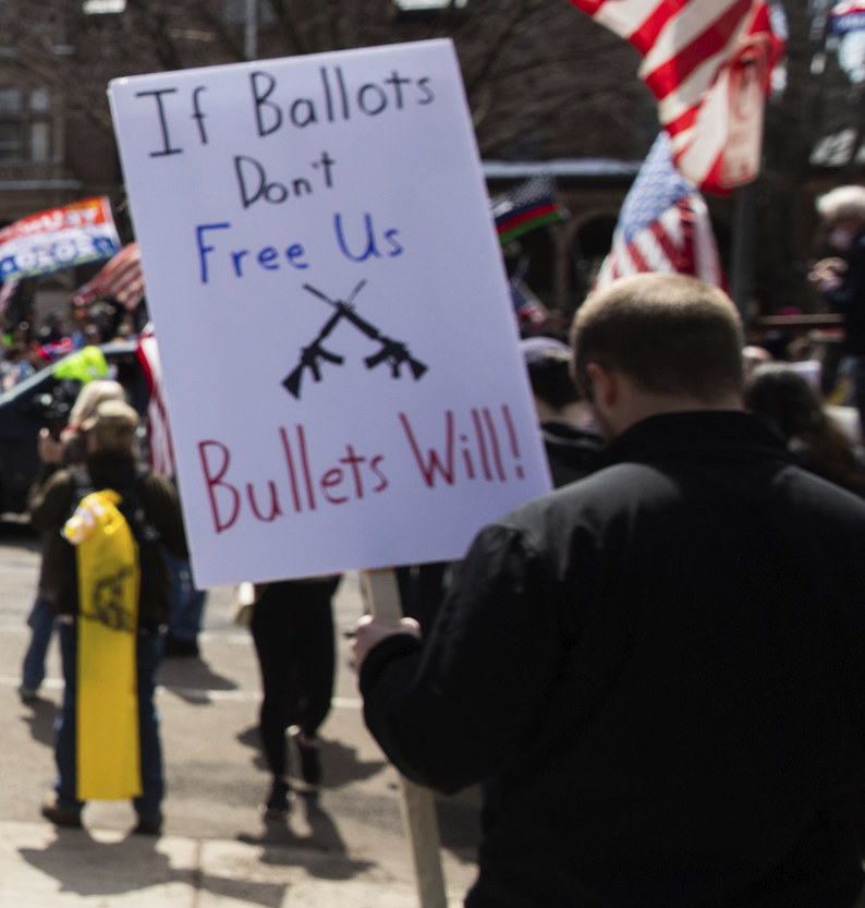 """Person holding a sign reading, """"If ballots don't free us bullets will!"""""""
