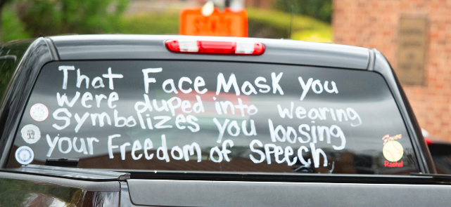"""Back of a car with the words, """"That face mask you were duped into wearing symbolizes you loosing [sic] your freedom of speech"""""""
