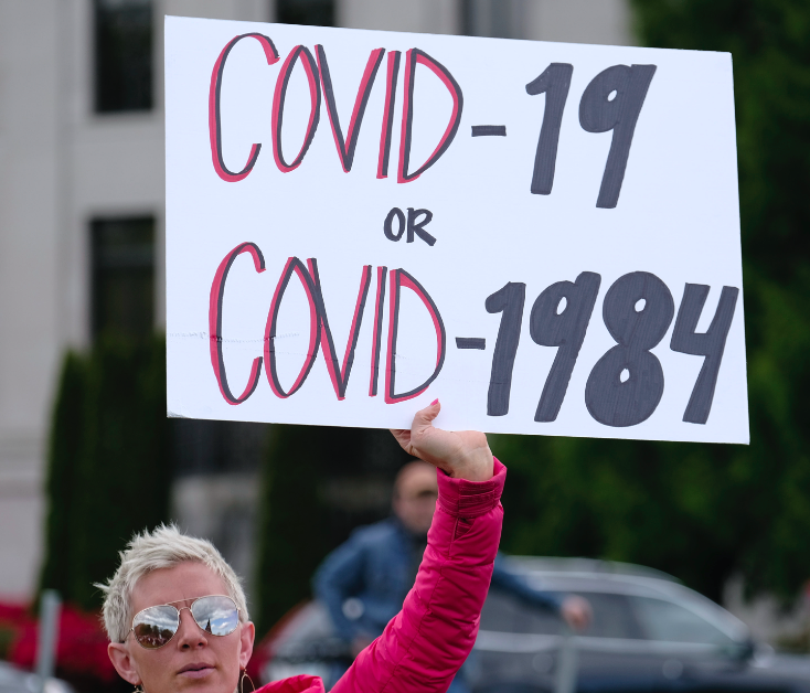 """Person holding up a sign reading, """"COVID-19 or COVID-1984"""""""