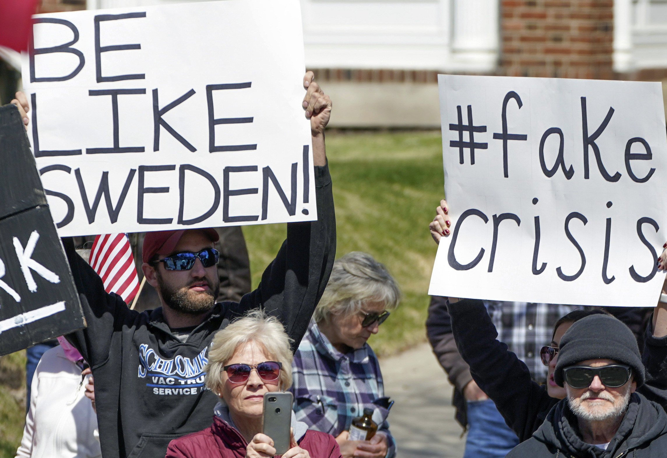 """A man holding up a sign reading, """"Be like Sweden!"""" and another man with a sign reading, """"#fake crisis"""""""