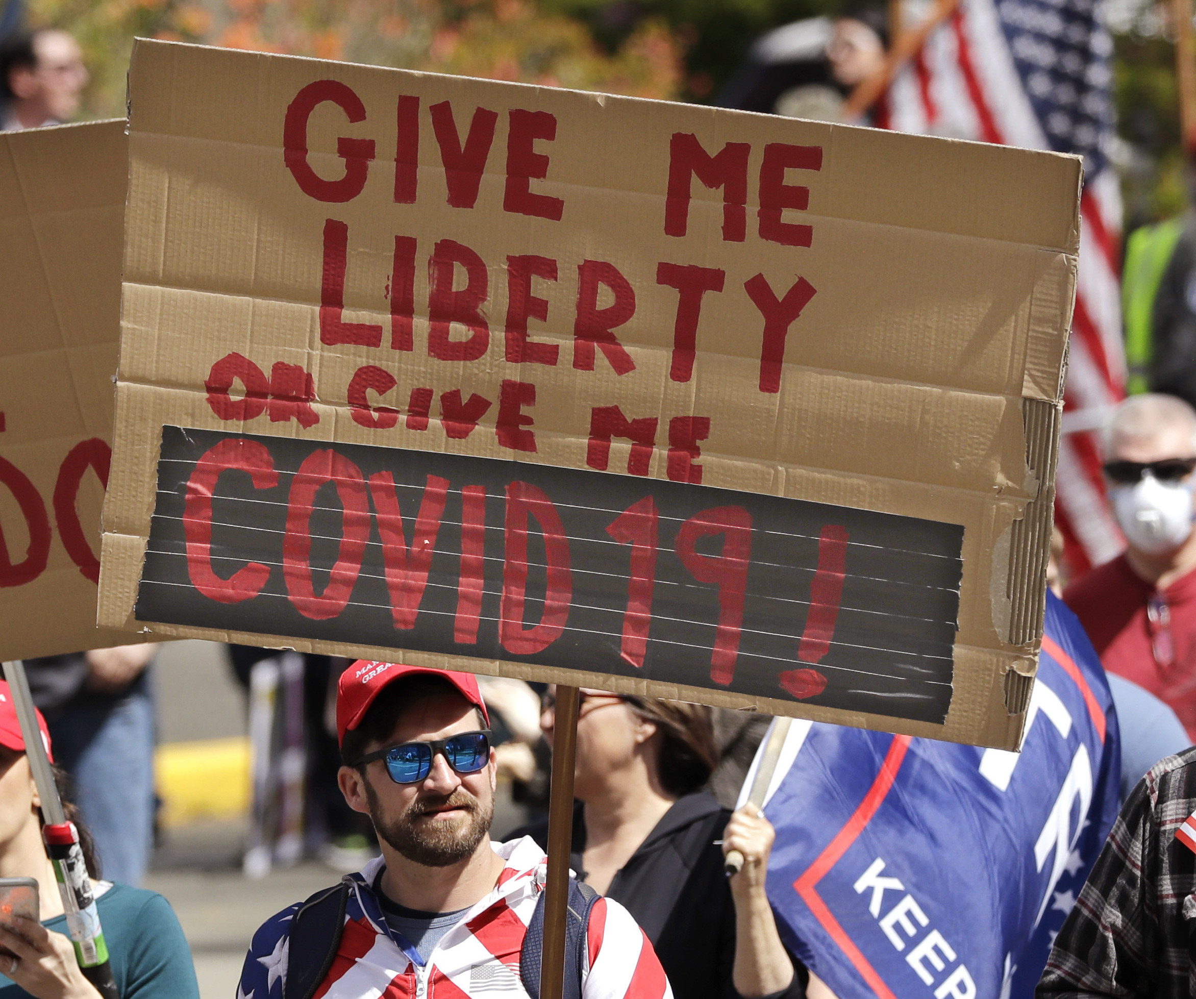 """Man holding a sign reading, """"Give me liberty or give me COVID 19!"""""""