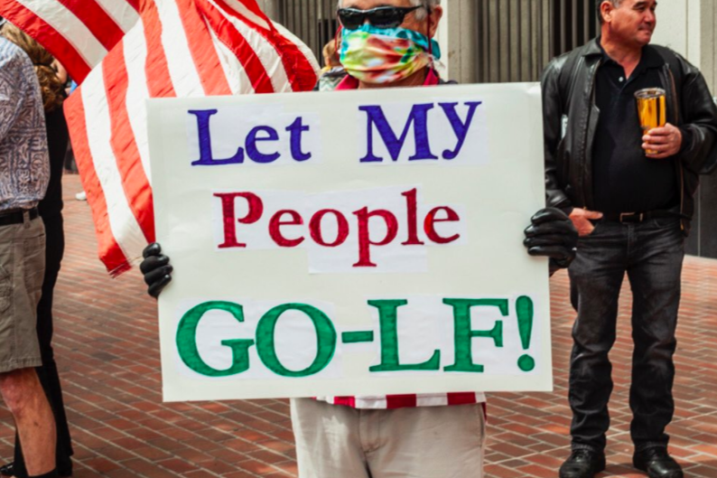 """Person wearing a colorful mask and holding a sign reading, """"Let my people go-lf!"""""""