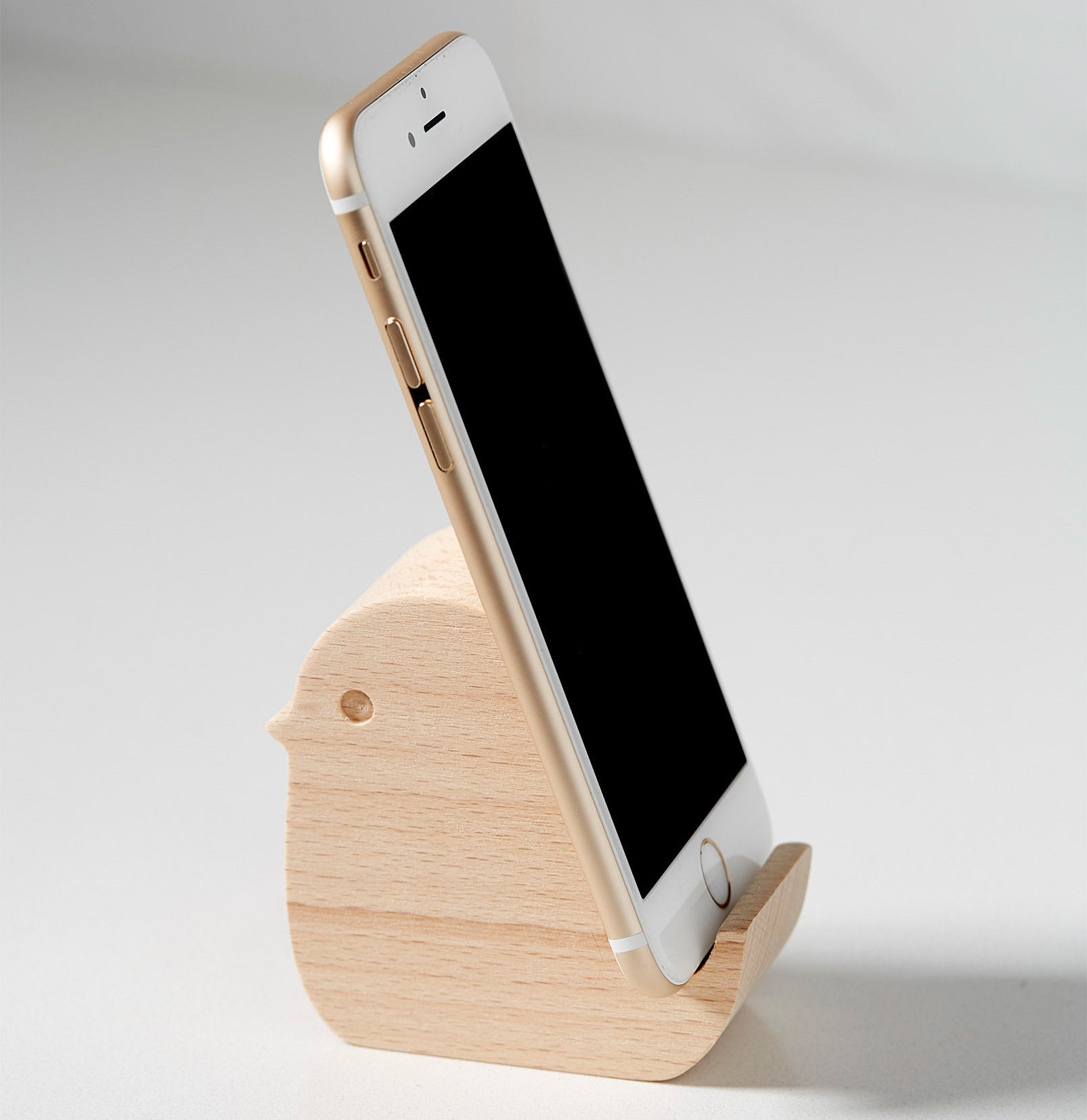 A wooden phone holder in the shape of a small bird