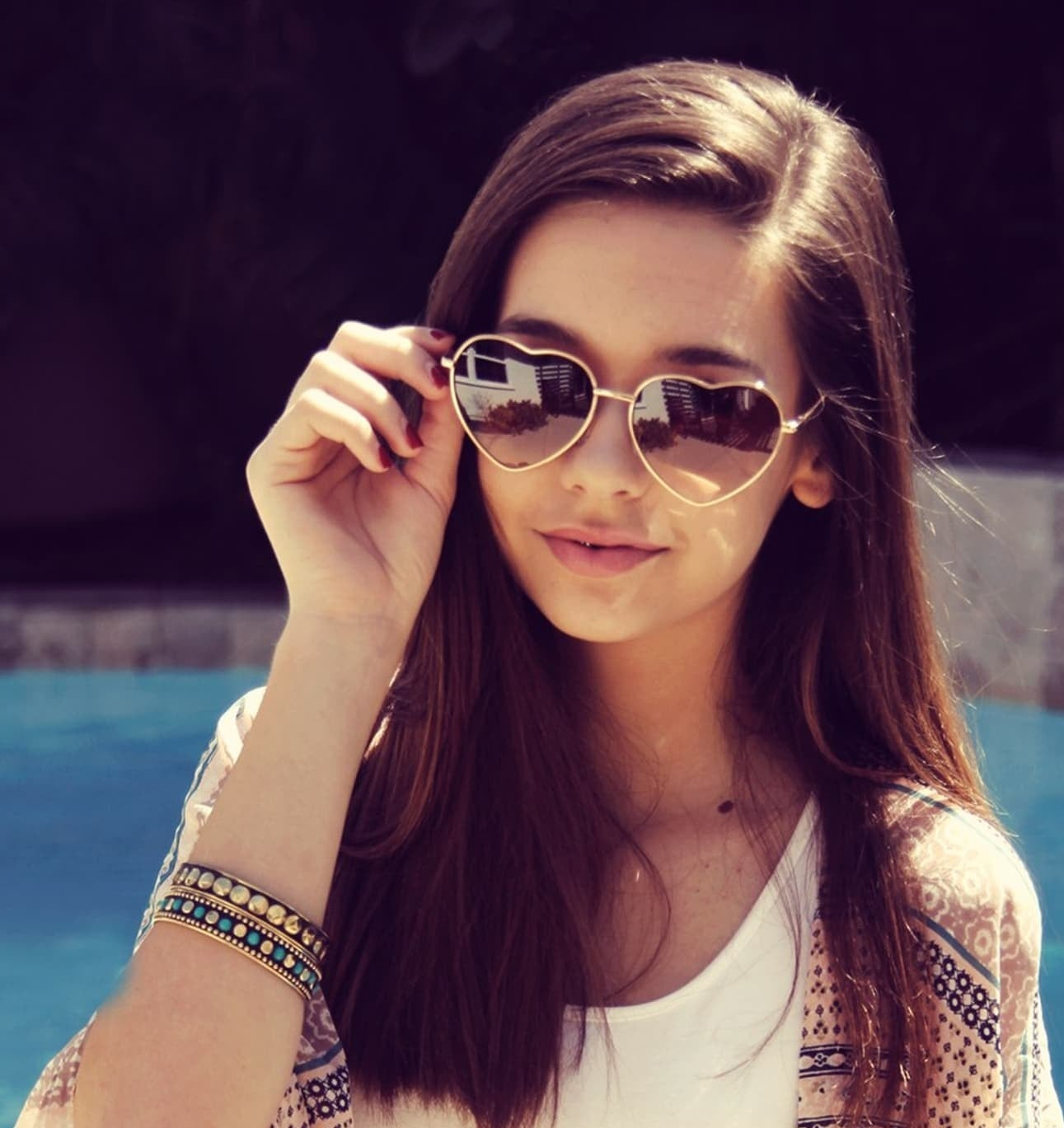 Model wearing the sunglasses with heart-shaped frames in gold and brown lenses