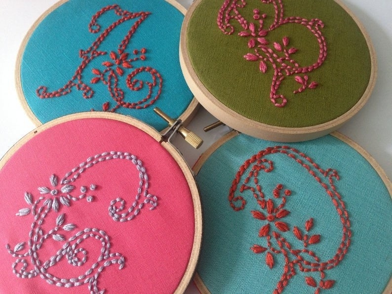 Several embroidery hoops with a different decorative letter on each one