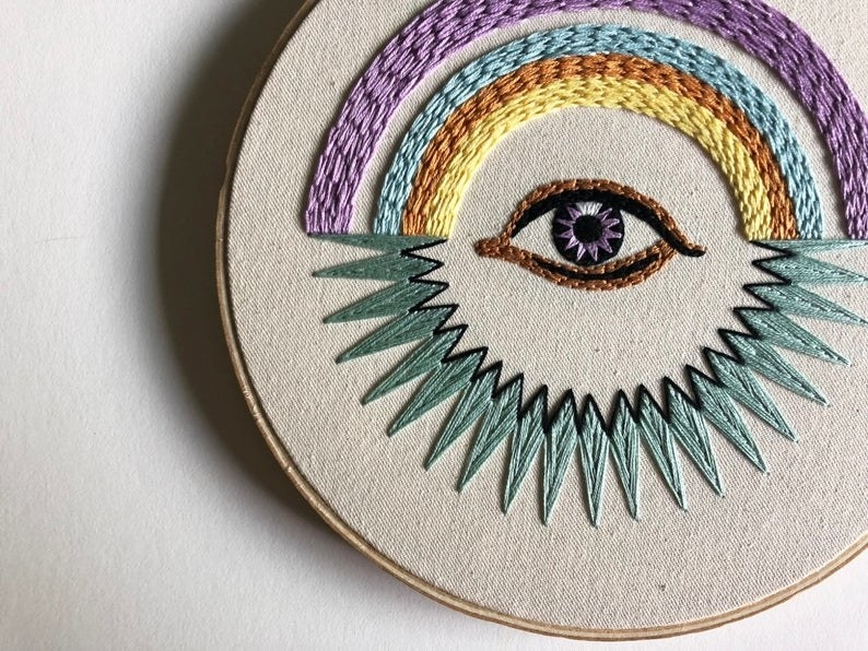 An eye with a rainbow above it and sun beam design below it