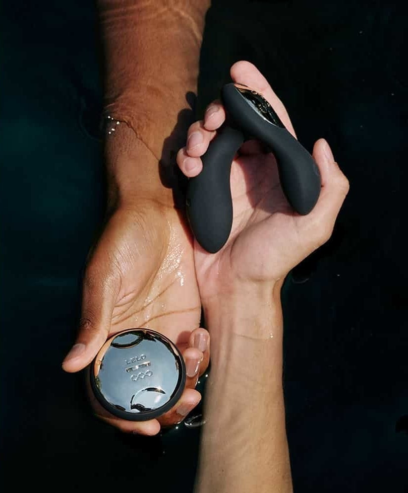 Two hands, one holding the dual ended prostate massage and the other holding a round silver remote