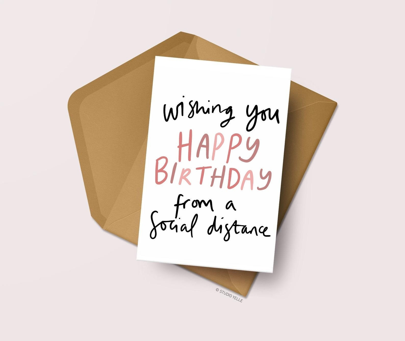 "A card that says ""wishing you a happy birthday from a social distance"" with an envelope"