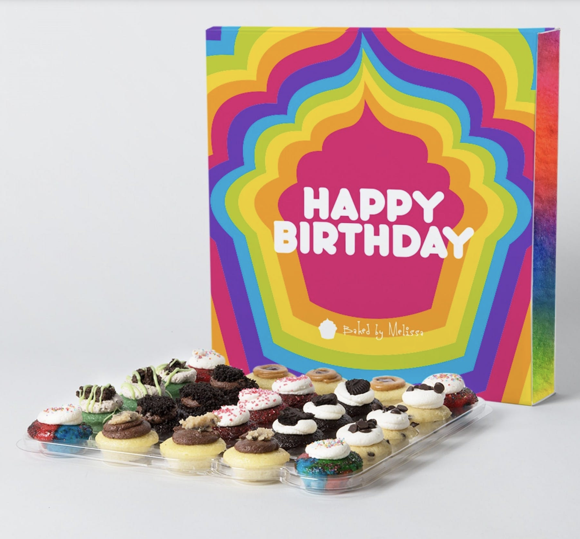 "The bite-sized cupcakes in a transparent holder next to a box that says ""Happy Birthday"""
