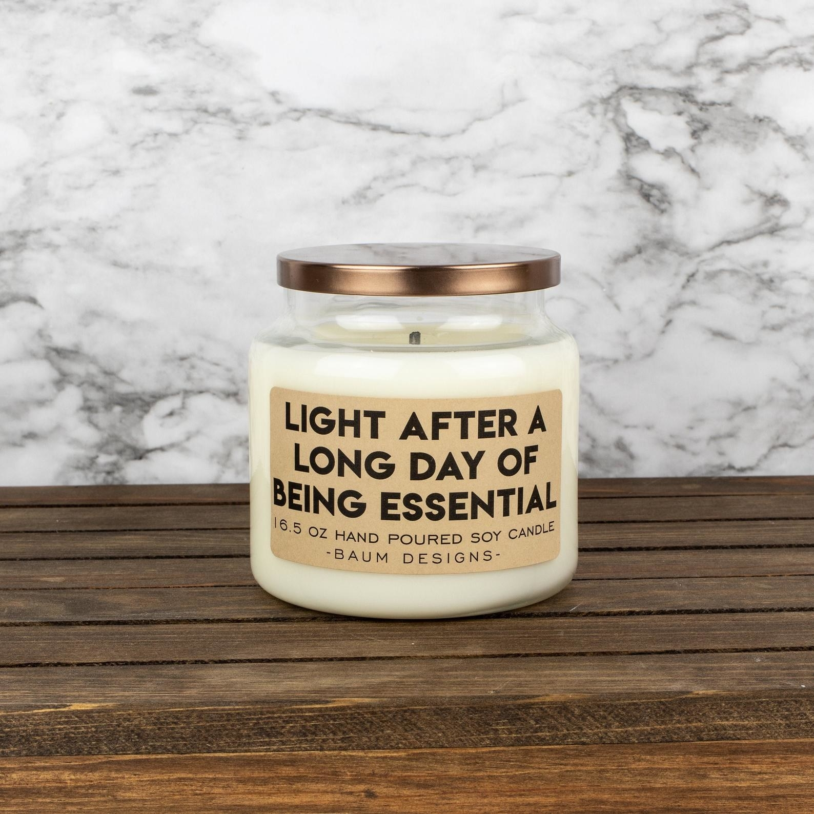 """A candle that says """"Light after a long day of being essential"""" on the front. It has a twist-off lid."""