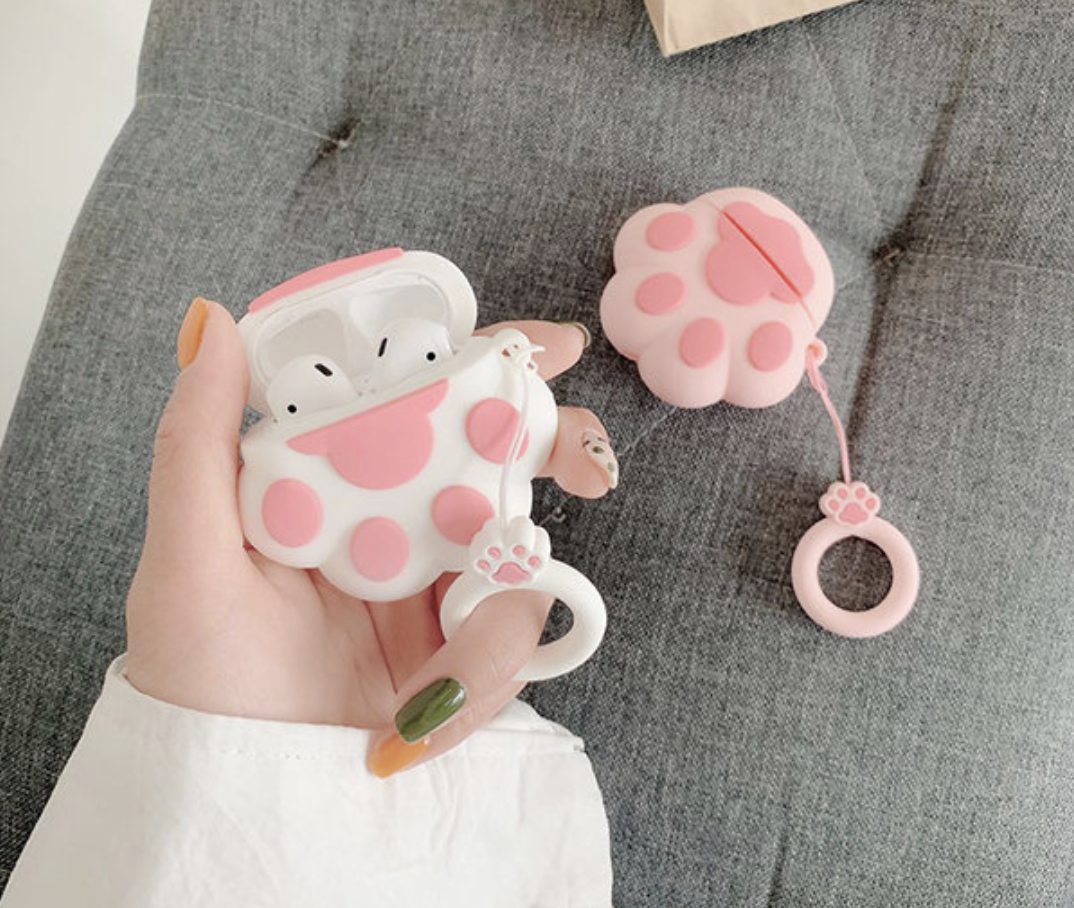 A person holding an AirPods case shaped like a paw print in white and pink, with another variation in pink and light pink resting on a cushion below it