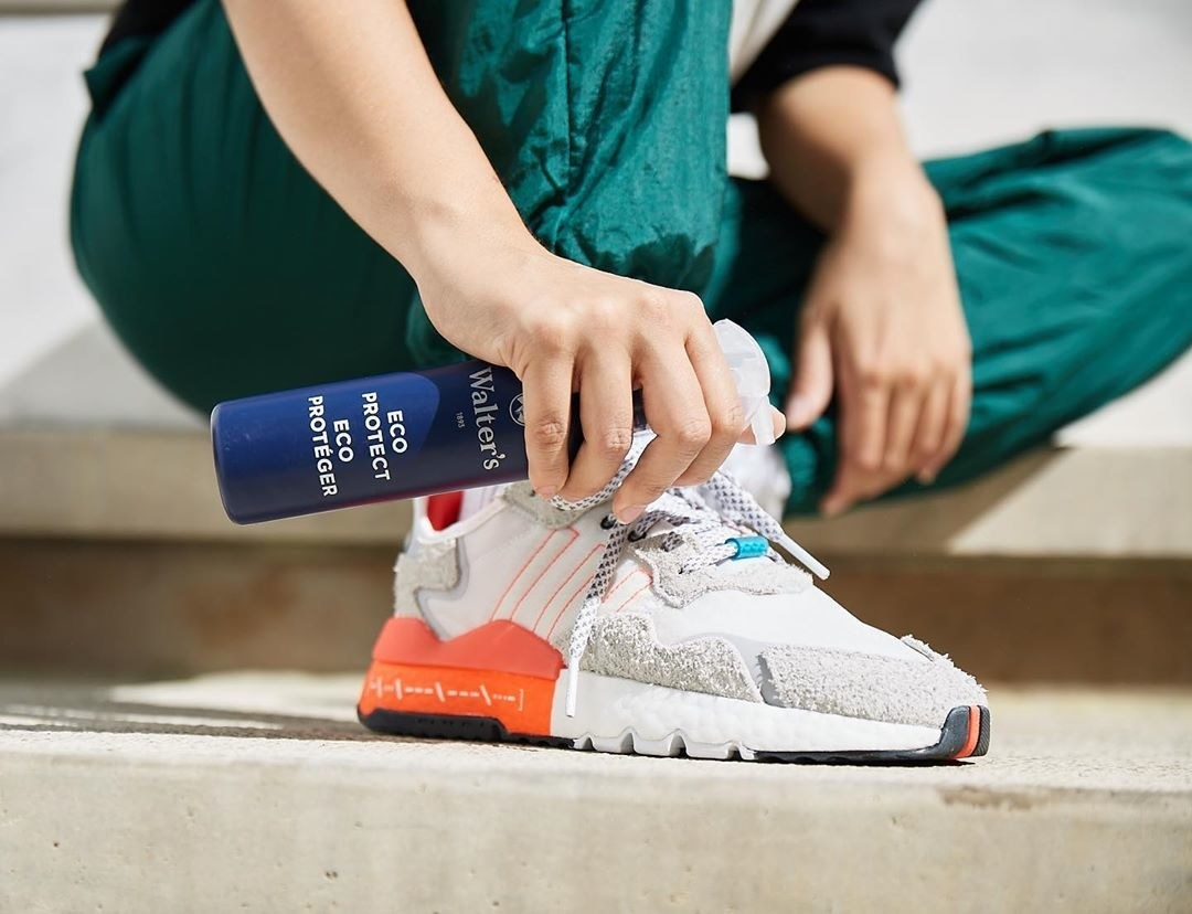A person spraying the shoe-protecting spray onto their sneaker